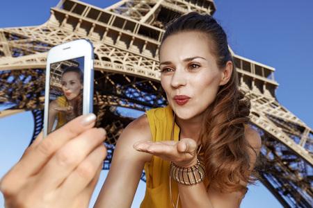 Touristy, 의심의 여지가 있지만, 아직 재미. 파리, 프랑스에서 에펠 타워의 앞에서 스마트 키와 selfie을 복용 하 고 공기 키스를 날리는 행복 한 젊은 여자 스톡 콘텐츠