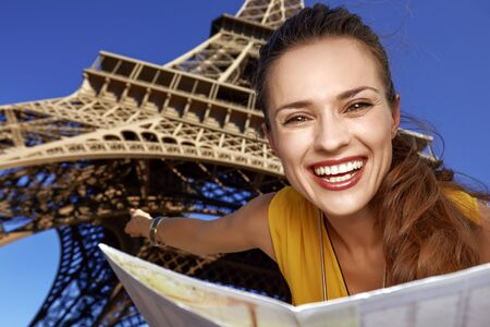 Touristy, without doubt, but yet so fun. Portrait of smiling young woman holding map and pointing in the front of Eiffel tower in Paris, France Stok Fotoğraf