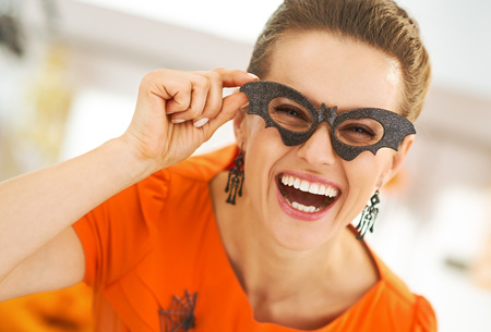 Frightful Treats all the way. Portrait of smiling young woman in party bat glasses in the Halloween decorated kitchen