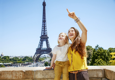 Having fun time near the world famous landmark in Paris. Portrait of happy mother and child pointing on something against Eiffel tower