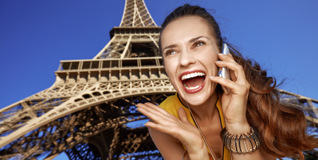 Touristy, without doubt, but yet so fun. surprised young woman talking on a mobile phone in the front of Eiffel tower in Paris, France