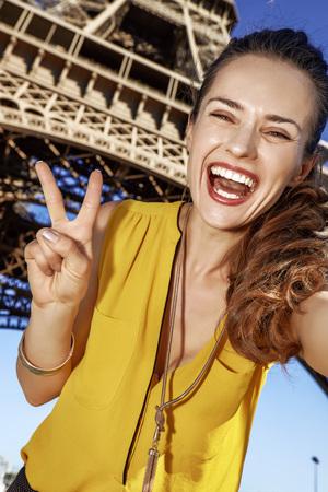 Touristy, 의심의 여지가 있지만, 아직 재미. 셀카 복용 및 파리, 프랑스에서 에펠 탑에 대하여 승리를 보여주는 행복 한 젊은 여자