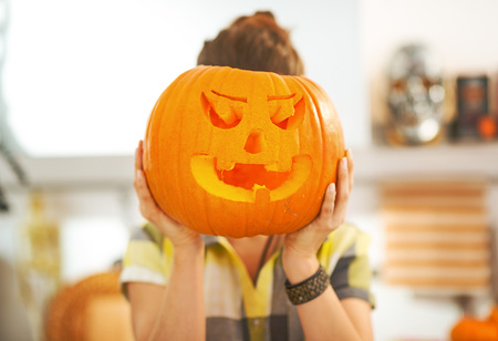 Frightful Treats on the way. Portrait of housewife in the Halloween decorated kitchen holding a big orange pumpkin Jack-O-Lantern in front of head