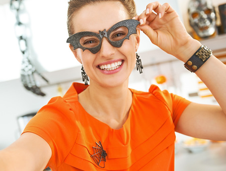 Frightful Treats all the way. smiling young woman in party bat glasses in the Halloween decorated kitchen taking selfie