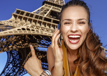 Touristy, without doubt, but yet so fun. Portrait of happy young woman speaking on a cell phone and pointing in the front of Eiffel tower in Paris, France Stok Fotoğraf