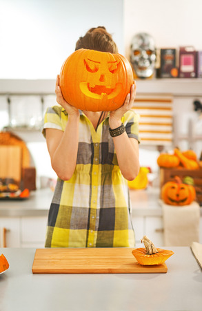 Frightful Treats on the way. young woman in the Halloween decorated kitchen holding a big orange pumpkin Jack-O-Lantern in front of head Stock Photo