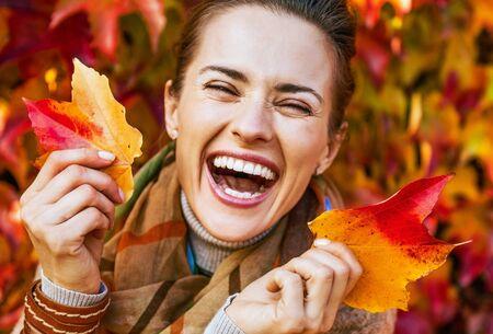 행복 한 젊은 여자의 초상화 leafs 단풍 앞의