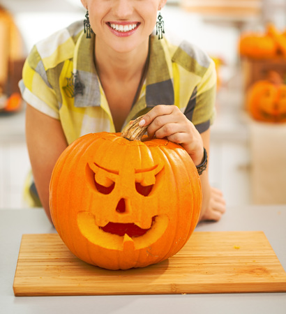 Frightful Treats on the way. Closeup on smiling young woman in the Halloween decorated kitchen with a big orange pumpkin Jack-O-Lantern Stock Photo