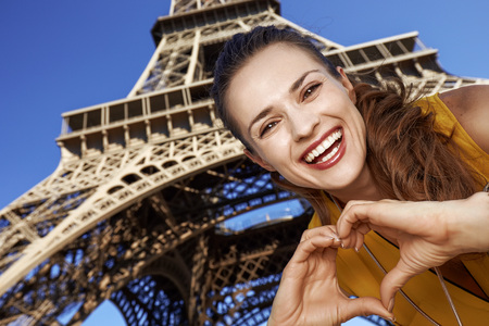 Touristy, without doubt, but yet so fun. smiling young woman showing heart shaped hands in the front of Eiffel tower in Paris, France Stok Fotoğraf