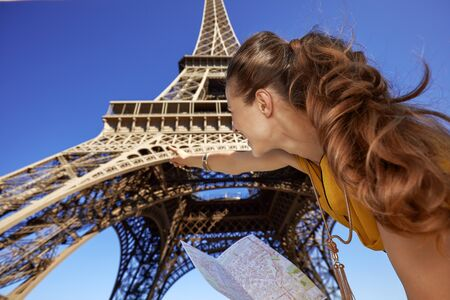 Touristy, without doubt, but yet so fun. Seen from behind young woman holding map and pointing on Eiffel tower in Paris, France