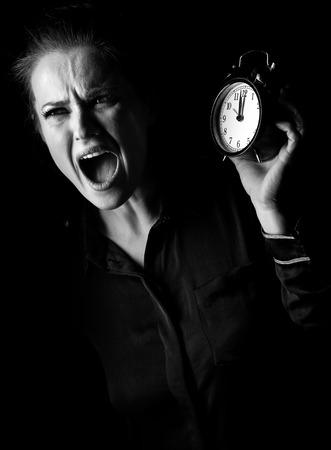 ? Wegwezen in het licht. benadrukt vrouw in de donkere jurk geïsoleerd op zwarte achtergrond met wekker