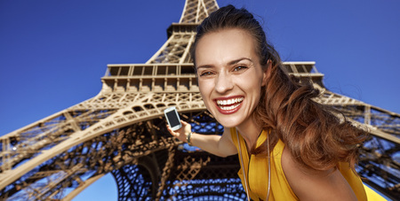Touristy, without doubt, but yet so fun. Portrait of happy young woman taking selfie with smartphone against Eiffel tower in Paris, France