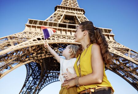 Touristy, without doubt, but yet so fun. smiling mother and daughter travellers rising flag against Eiffel tower in Paris, France