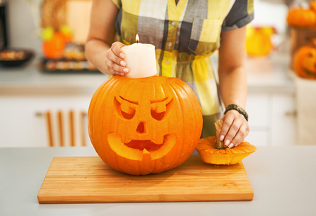 Frightful Treats on the way. Closeup on woman in the Halloween decorated kitchen putting candle inside a big orange pumpkin Jack-O-Lantern