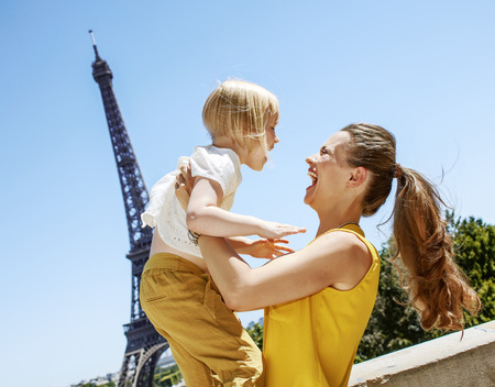 Having fun time near the world famous landmark in Paris. happy mother and child having fun time against Eiffel tower