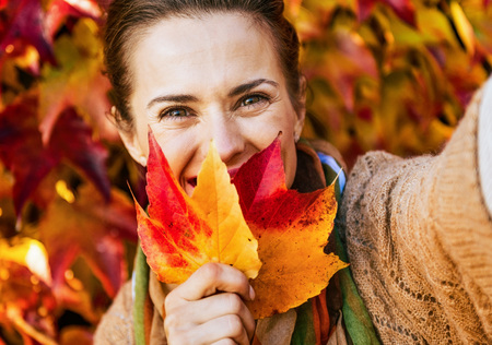 Happy young woman hiding behind leaf while making selfie in front of autumn foliage Stock Photo