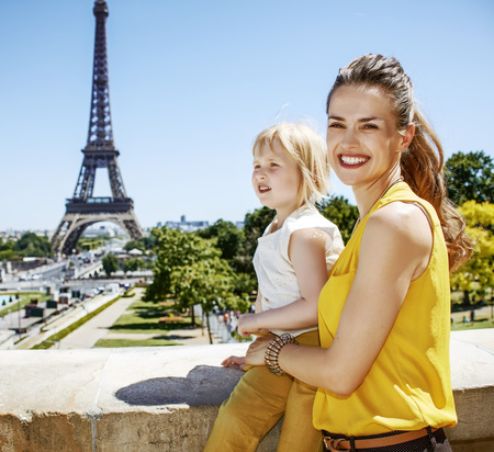 Having fun time near the world famous landmark in Paris. smiling mother and daughter travellers looking into the distance in Paris, France