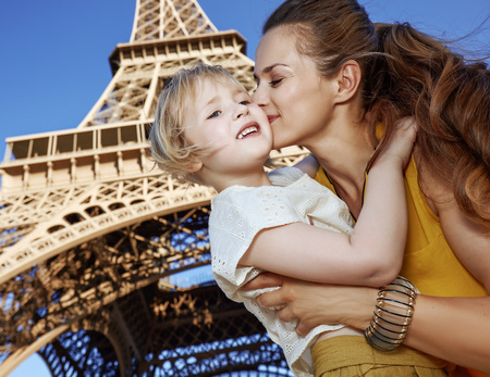 Touristy, without doubt, but yet so fun. happy mother and child tourists kissing against Eiffel tower in Paris, France Stok Fotoğraf