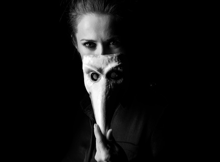 venice: ?oming out into the light. Portrait of woman in the dark dress isolated on black hiding behind Venetian mask