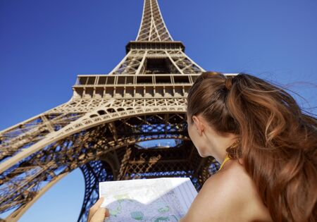 Touristy, without doubt, but yet so fun. Seen from behind young woman with map against Eiffel tower in Paris, France Stock Photo