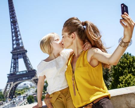 Plezier hebben in de buurt van het wereldberoemde oriëntatiepunt in Parijs. moeder en dochter toeristen nemen selfie met digitale camera en kussen in Parijs, Frankrijk