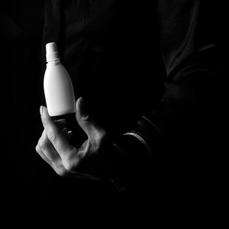 Black Mania. female hand isolated on black background showing bottle of medical drops Stock Photo - 83756339