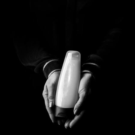 Black Mania. female hands isolated on black showing a bottle of cosmetics