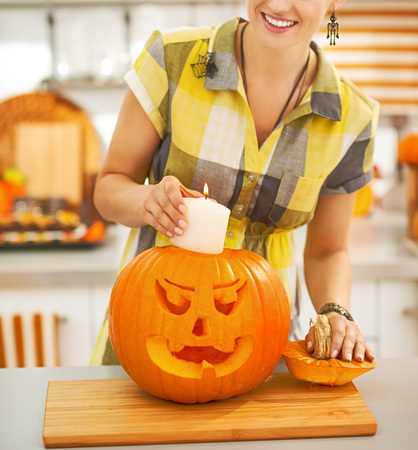 Frightful Treats on the way. happy modern housewife in the Halloween decorated kitchen putting candle inside a big orange pumpkin Jack-O-Lantern