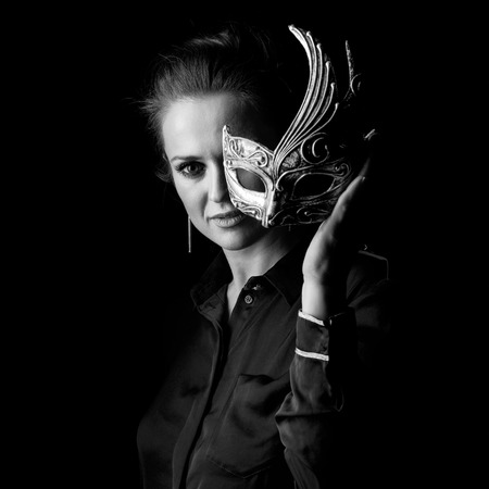 ?oming out into the light. Portrait of woman in the dark dress isolated on black background holding Venetian mask Stock Photo
