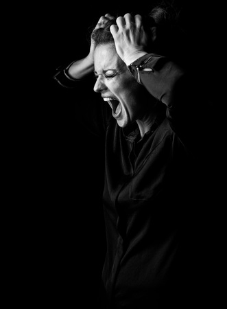 ?oming out into the light. Portrait of angry woman in the dark dress isolated on black background Stock Photo