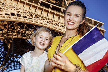 Touristy, without doubt, but yet so fun. Portrait of happy mother and daughter tourists showing flag against Eiffel tower in Paris, France Stok Fotoğraf