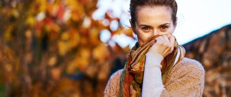 젊은 여자가 저녁에 스카프에 숨어 스톡 콘텐츠 - 83771579