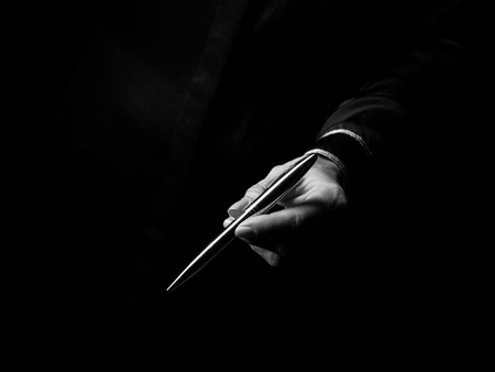 Black Mania. female hand isolated on black giving a pen