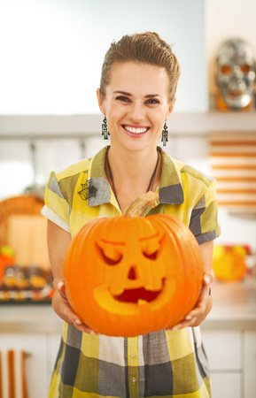 Frightful Treats on the way. Portrait of happy modern housewife in the Halloween decorated kitchen showing big pumpkin Jack-O-Lantern
