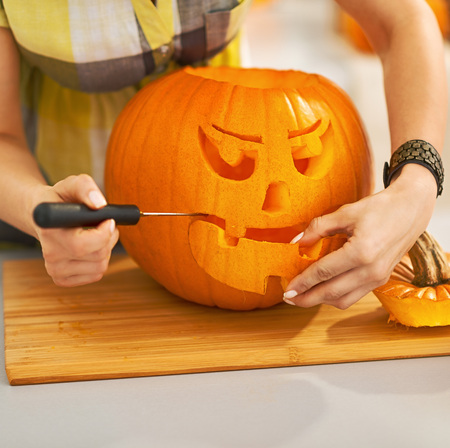 Frightful Treats on the way. Closeup on housewife in the Halloween decorated kitchen carving a big orange pumpkin Jack-O-Lantern