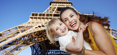 Touristy, without doubt, but yet so fun. Portrait of smiling mother and child tourists against Eiffel tower in Paris, France