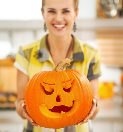 Frightful Treats on the way. Smiling modern housewife in the Halloween decorated kitchen showing big pumpkin Jack-O-Lantern. Closeup