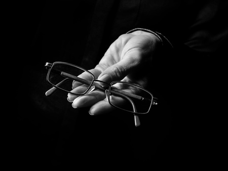 Black Mania. female hand isolated on black showing spectacles