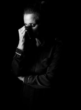 ? 빛을 밖으로 oming. 블랙에 고립 된 어두운 드레스에 스트레스를 된 여자의 초상화 스톡 콘텐츠
