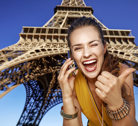Touristy, without doubt, but yet so fun. happy young woman showing thumbs up and speaking on a mobile phone against Eiffel tower in Paris, France Stok Fotoğraf