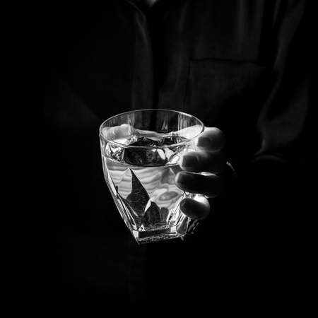 blackwhite: Black Mania. female hand isolated on black showing glass of water Stock Photo