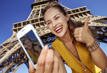 Touristy, 의심의 여지가 있지만, 아직 재미. 파리, 프랑스에서 에펠 타워의 앞에 휴대 전화와 함께 selfie을 복용 웃는 젊은 여자