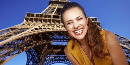 Touristy, without doubt, but yet so fun. Portrait of smiling young woman in the front of Eiffel tower in Paris, France