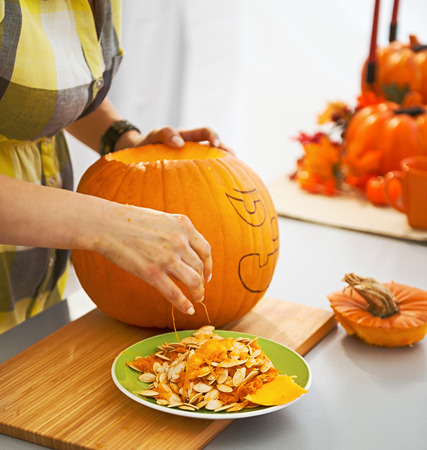 Frightful Treats on the way. Closeup on young housewife in the Halloween decorated kitchen prepare big orange pumpkin for carving