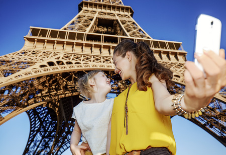 Touristy, without doubt, but yet so fun. happy mother and daughter tourists taking selfie  with smartphone against Eiffel tower in Paris, France Stok Fotoğraf