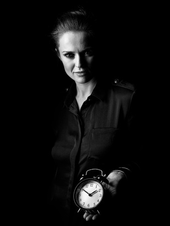 ?oming out into the light. Portrait of woman in the dark dress isolated on black showing alarm clock