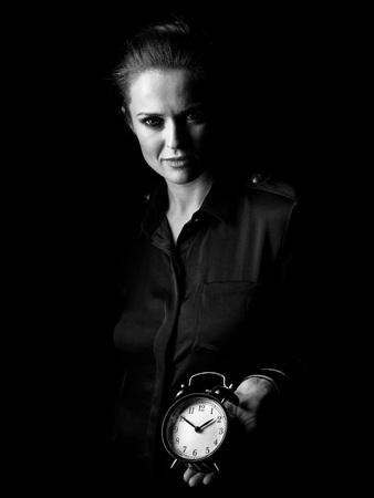 ? Wegwezen in het licht. Portret van vrouw in de donkere die kleding op zwarte wordt geïsoleerd die wekker tonen