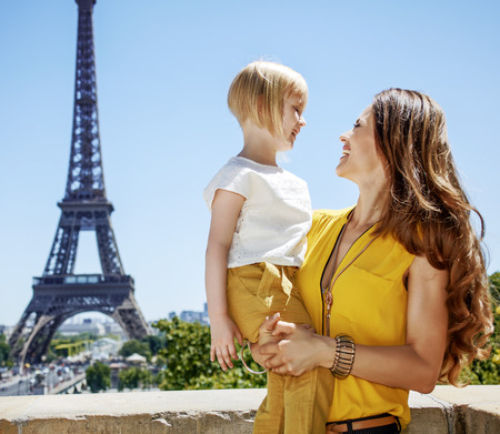 Having fun time near the world famous landmark in Paris. Portrait of smiling mother and daughter travellers looking at each other in Paris, France