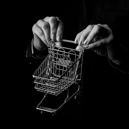 Black Mania. woman hands isolated on black showing mall shopping cart Stock Photo