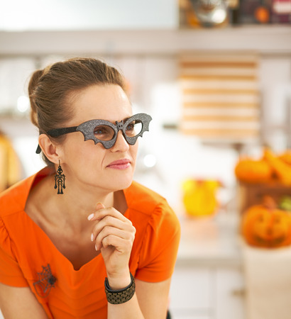 Frightful Treats all the way. Portrait of young woman in party bat glasses in the Halloween decorated kitchen looking aside